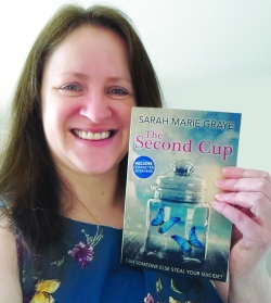 Sarah Marie Graye holding a paperback copy of The Second Cup
